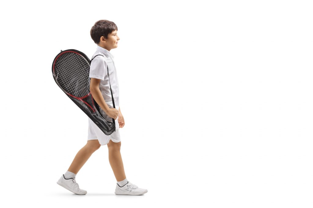 Boy walking with tennis racket in cover